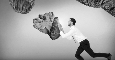 Digital composite of businessman pushing surreal rocks suspended in the air