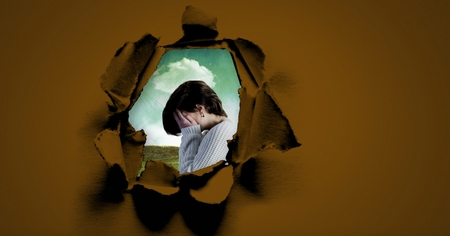 Digital composite of distressed woman holding hands in face through surreal paper hole