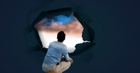 Digital composite of man looking through surreal paper hole at sky
