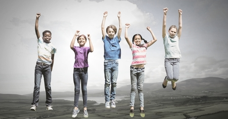 Digital composite of children jumping for joy into sky with natural landscape Stock Photo