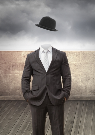 Digital composite of Headless man with surreal floating hat in front of wall Stock Photo