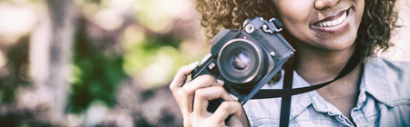 Portrait of smiling woman with digital camera standing at park