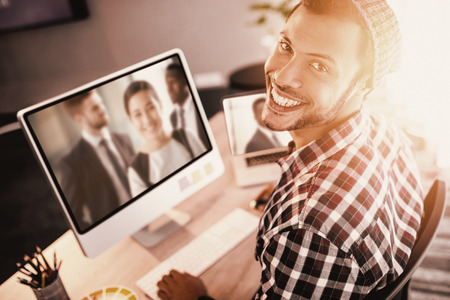 Portrait of man smiling while sitting by computer against happy businesswoman in office