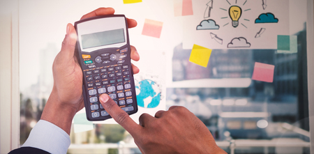Cropped hands of businessman using calculator  against adhesive notes on window
