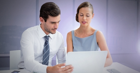 Digital composite of Business couple working on laptop