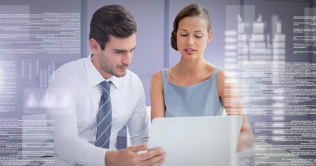 Digital composite of Business couple working on laptop with screen text interface Stock Photo