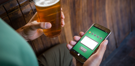 Satisfaction against cropped hands of man using phone while having beer Stock Photo