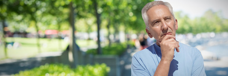 close up of thoughtful senior man with hand on chin against blur view of park