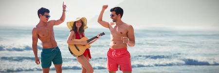 Teenagers dancing and playing music  against scenic view of beach