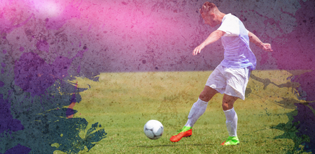 Male soccer player playing football against dirty old wall background Stock Photo