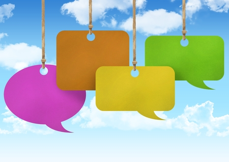 Digital composite of Hanging paper speech bubbles and sky background Stock Photo