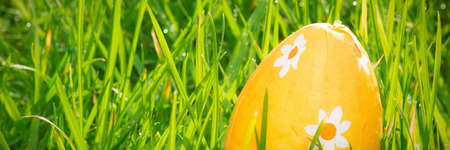Orange foil wrapped easter egg in the grass