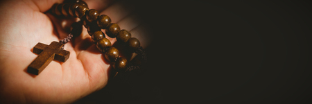 Close-up of hand holding rosary beads Stockfoto