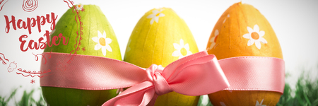 Happy easter against three easter eggs wrapped in pink ribbon Stock Photo