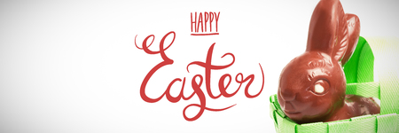 happy easter graphic against chocolate bunny in a basket