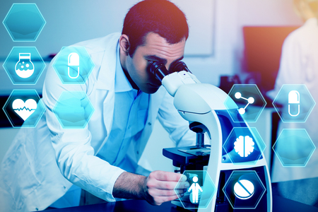 Medecine against science student looking through microscope Stock Photo
