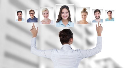 Digital composite of Woman touching portrait profiles of different people Stock Photo