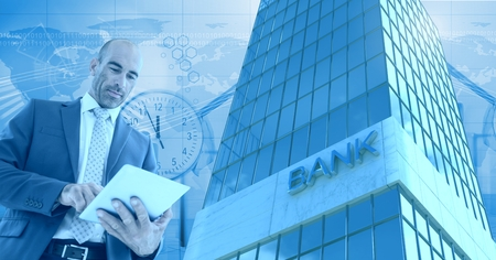 Digital composite of Businessman using tablet with Tall building bank with time and world people icons Banco de Imagens