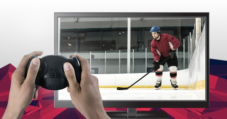 Digital composite of Hands holding gaming controller  with ice hockey player on television 免版税图像