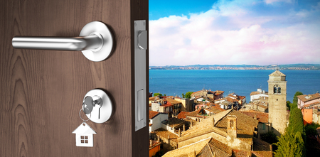 Digitally generated image of brown door with key against sky view of a village in front of the sea