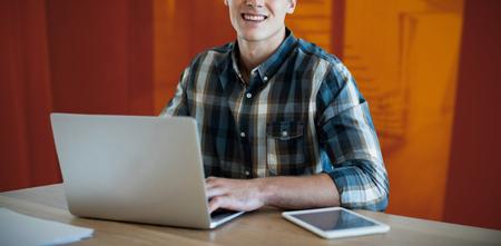Portrait of businessman using laptop at desk against staircase in modern office 版權商用圖片