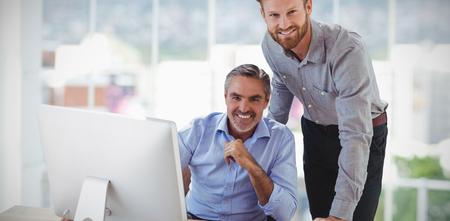 Portrait of smiling businessmen at desk against digitally generated image of buildings