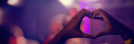 Cropped image of fan in audience forming heart shape during stage show in nightclub Stock fotó