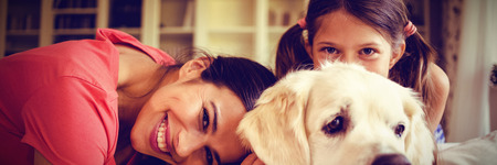 Mother and daughter with dog sitting in living room at home