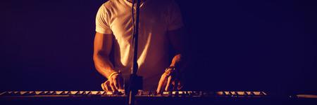 Man singing while playing piano at nightclub Stok Fotoğraf