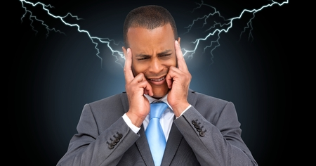Digital composite of Lightning strikes and stressed man with headache holding head
