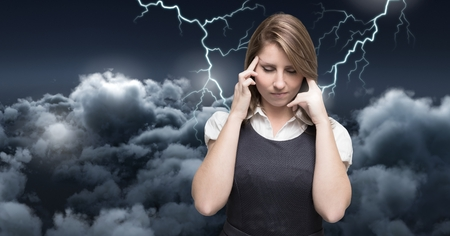 Digital composite of Lightning strikes and stressed woman with headache holding head Stock Photo