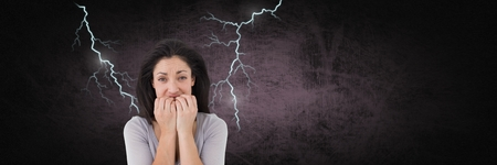 Digital composite of Lightning strikes and scared afraid woman biting nails
