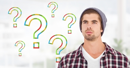 Digital composite of Man thinking with colorful question marks Stock Photo