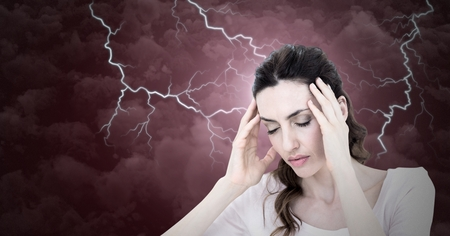 Digital composite of Lightning strikes and stressed woman with headache holding head Imagens