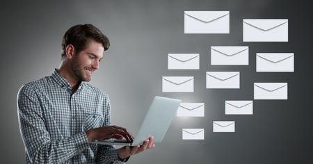 Digital composite of Envelope letter messages and man using laptop