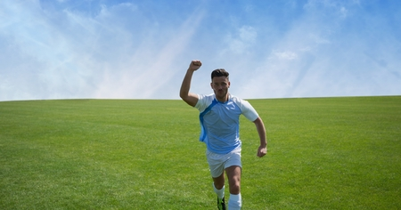 Digital composite of Soccer player on grass with sky