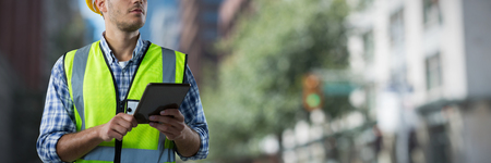 Concentrated Construction Worker With Tablet against blur view of a modern city Stock Photo