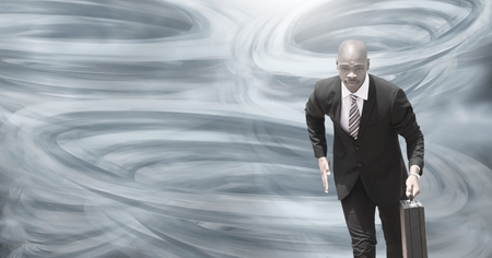 Digital composite of Tornado twisters painted and dark sky with businessman running