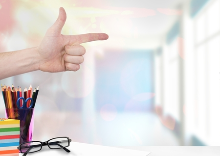 Digital composite of hand pointing with education objects Stock Photo