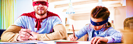 Father and son pretending to be superhero while studying Stock Photo