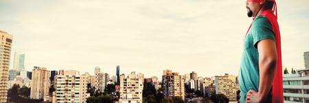 Man pretending to be a superhero against city against blue sky