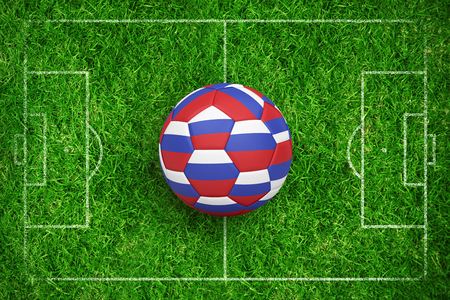Football in russia colours against closed up view of grass