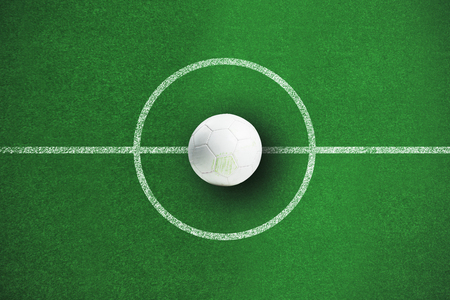 White leather football with grass stains against soccer field plan Stock Photo