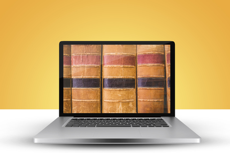 Laptop with with screen against close up of old books