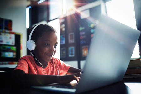Boy listening music while using laptop at desk in school