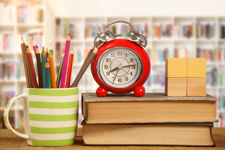 Alarm clock and books by colored pencils in mug on table against teacher reading books to her students Stock Photo