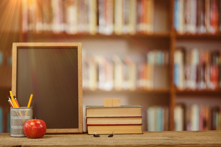 Books by slate with desk organizer and apple on wooden table against library shelf Stock Photo