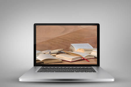 Laptop with with screen against various open book