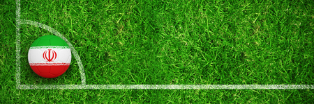 Football in iran colours against closed up view of grass