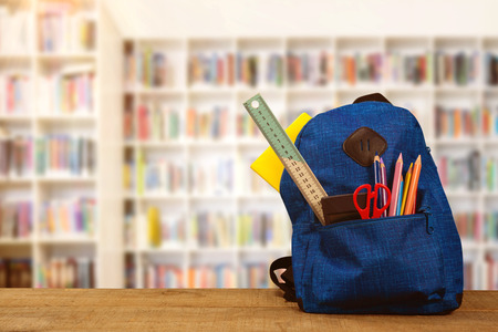 Schoolbag on wooden table against teacher reading books to her students